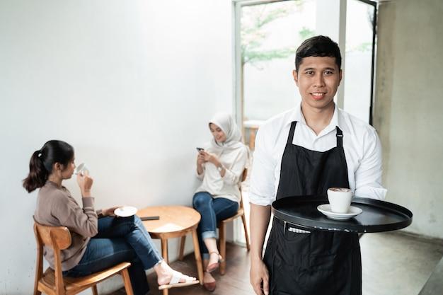 Uśmiechnięty kelner podaje filiżankę kawy