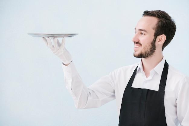 Uśmiechnięty kelner podnosi metalową tacę