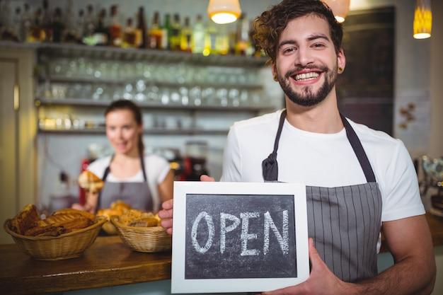 Uśmiechnięty kelner pokazano łupków z otwartym znakiem w caf