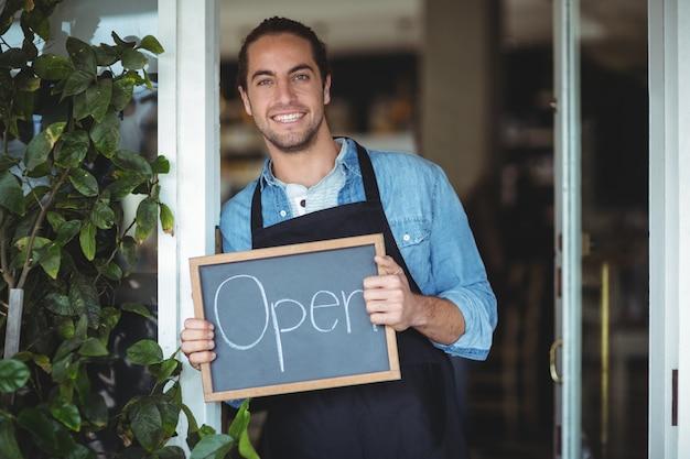 Uśmiechnięty kelner pokazuje tablicę z otwartym znakiem