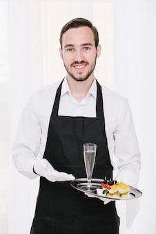 Uśmiechnięty kelner przedstawiający szampana