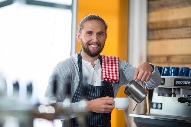 Uśmiechnięty kelner robi filiżance kawy przy kontuarem w kawiarni