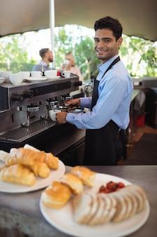 Uśmiechnięty kelner robi filiżankę kawy z ekspresu do kawy