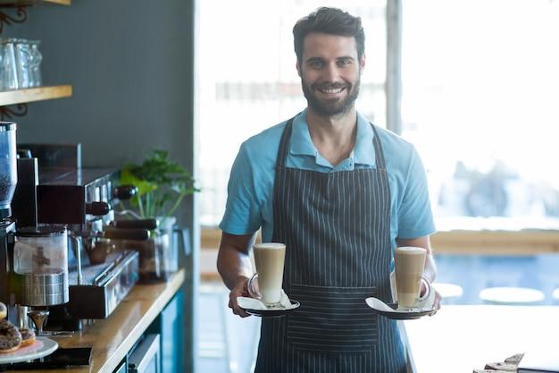 Uśmiechnięty kelner trzyma filiżankę zimna kawa przy kontuarem w kawiarni