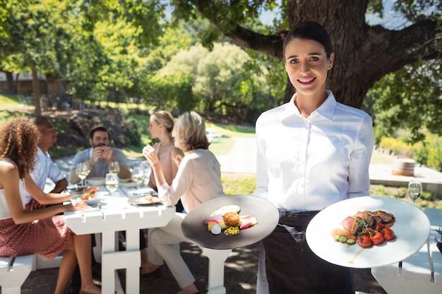 Uśmiechnięty kelner trzyma talerze z jedzeniem w restauracji