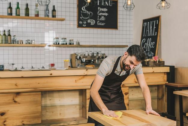 Uśmiechnięty kelnera obcierania stół