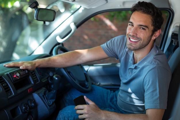 Uśmiechnięty kierowca siedzi w samochodzie