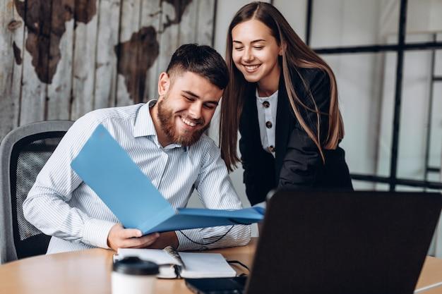 Uśmiechnięty kierownik i jego asystent pracują w biurze