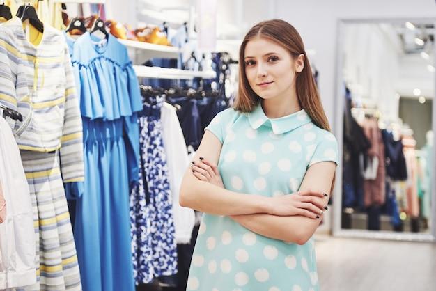 Uśmiechnięty kierownik sklepu przed jej butikiem
