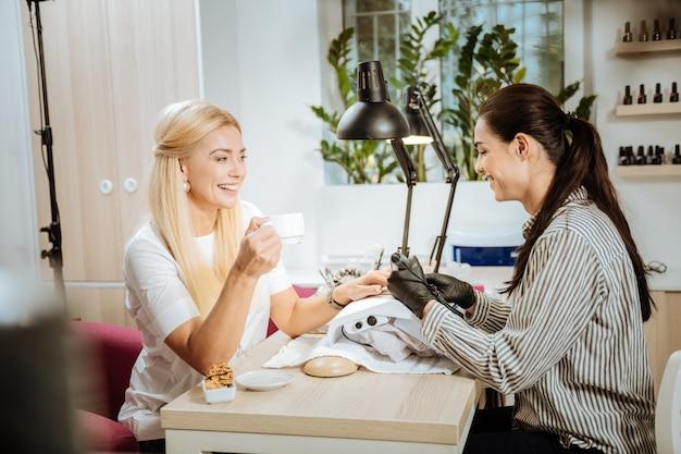 Uśmiechnięty klient. piękna blondynka klientka salonu piękności uśmiechnięta rozmawia z profesjonalną stylistką paznokci