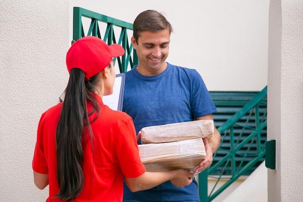Uśmiechnięty klient płci męskiej odbierania paczek. długowłosa dostawczyni rozdająca kartony szczęśliwemu klientowi. kobieta kurier w czerwonej koszuli dostarcza zamówienie i rozmawia. usługa dostawy i koncepcja poczty