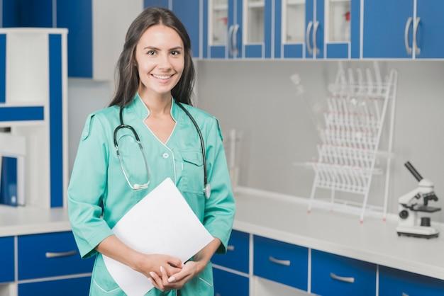 Uśmiechnięty kobieta student medycyny z papierami