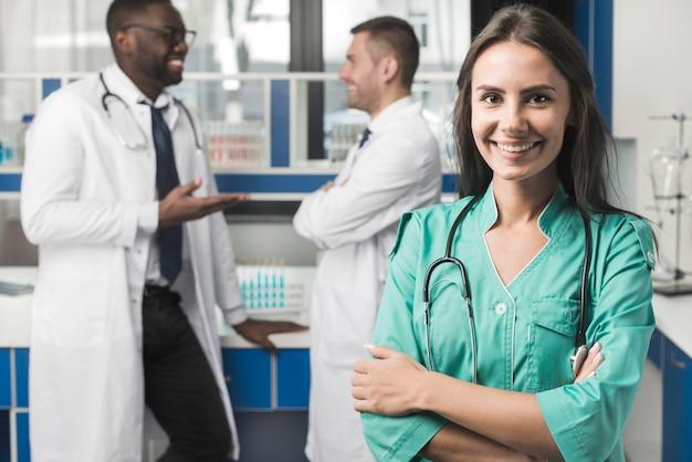 Uśmiechnięty kobieta student medycyny z rękami krzyżować