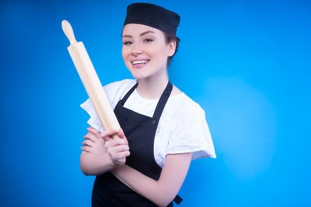 Uśmiechnięty kobieta szef kuchni w czarnym fartuchu stoi z drewnianym wałkiem
