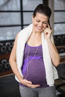 Uśmiechnięty kobieta w ciąży słuchająca muzyka i macanie jej brzuch przy gym