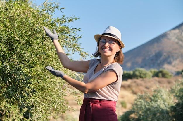 Uśmiechnięty kobieta właściciel oliwny ogród wskazuje drzewo