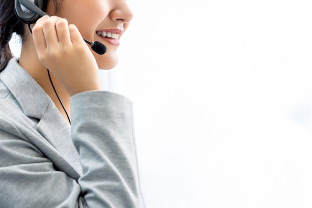 Uśmiechnięty kobiety centrum telefonicznego personel na biel ścianie z kopii przestrzenią