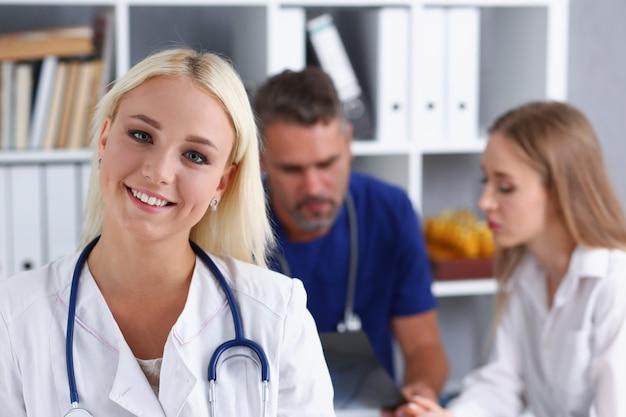Uśmiechnięty kobiety lekarki stojak w biurze