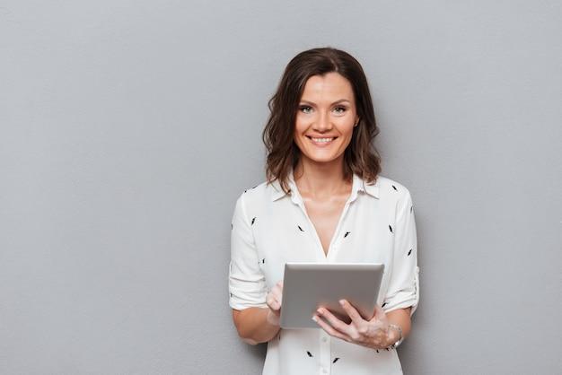 Uśmiechnięty kobiety mienia pastylki komputer w rękach i patrzeć kamerę na szarość