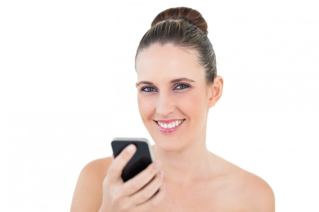 Uśmiechnięty kobiety mienia telefon patrzeje kamerę
