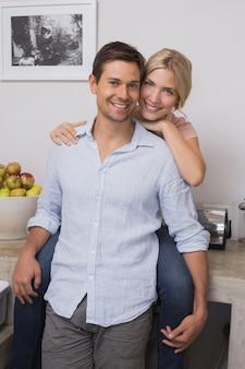 Uśmiechnięty kobiety obejmowania mężczyzna od behind w domu