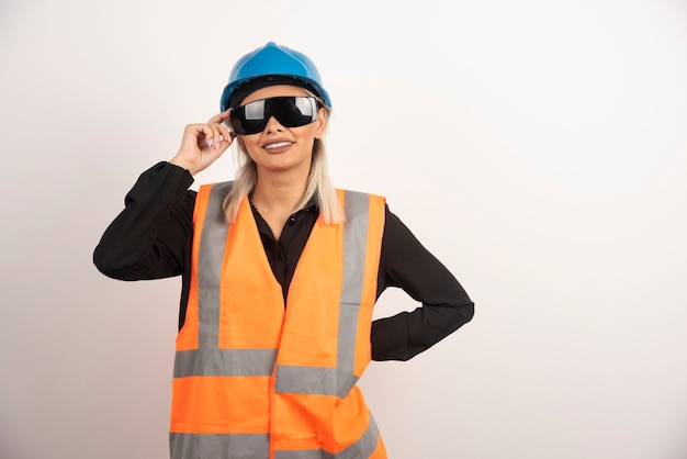 Uśmiechnięty konstruktor kobieta pozuje z gogle i hełmem. wysokiej jakości zdjęcie