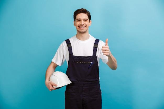 Uśmiechnięty konstruktor mężczyzna trzyma kask ochronny i pokazuje kciuk w górę, gdy nad niebieską ścianą