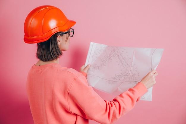 Uśmiechnięty konstruktor pracownik kobieta na różowym tle. hełm budowlany.
