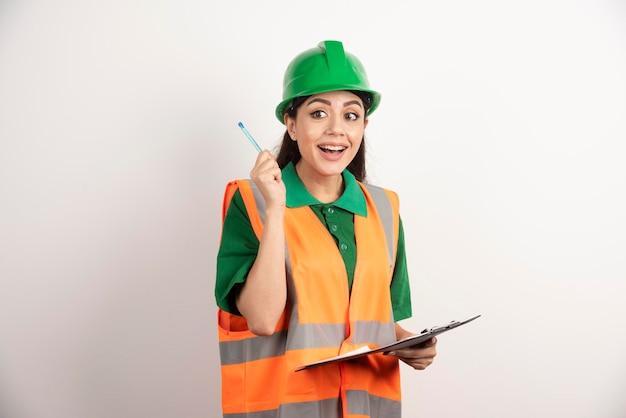 Uśmiechnięty konstruktor pracownik kobieta stojąc z ołówkiem i schowka. zdjęcie wysokiej jakości