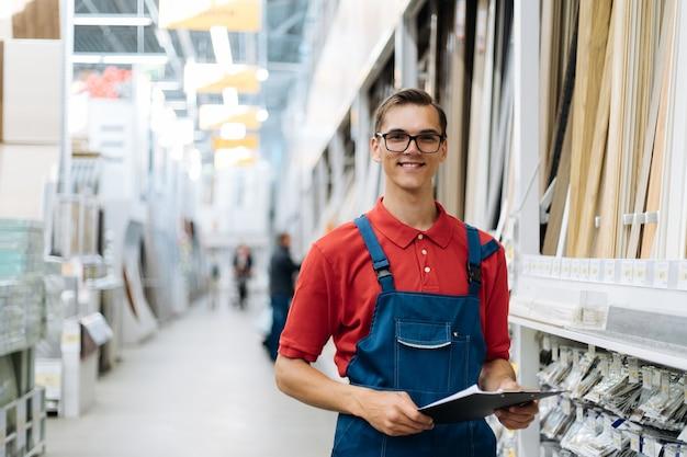 Uśmiechnięty konsultant sklepu z wykładzinami podłogowymi ze schowkiem stojącym w strefie sprzedaży