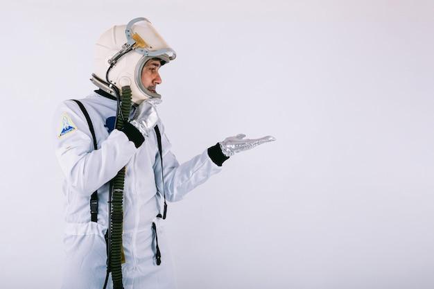 Uśmiechnięty kosmonauta mężczyzna w skafandrze i hełmie, wskazując ręką w prawo, na białym tle.