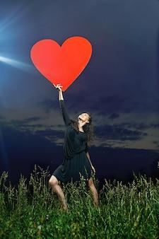 Uśmiechnięty, kręcone tancerz pozowanie na trawiastym boisku