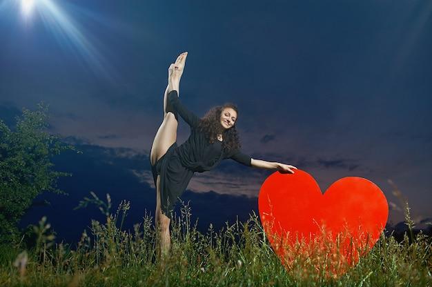 Uśmiechnięty, kręcone tancerz wykonuje pionowe podziały w trawiastym polu