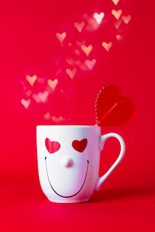 Uśmiechnięty kubek z czerwonym lizakiem i białymi serduszkami. koncepcja walentynki