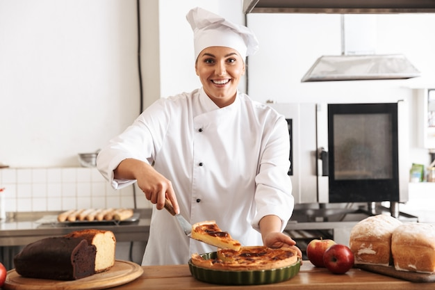 Uśmiechnięty kucharz kobieta ubrana w mundur wyświetlono gotowane ciasto stojąc w kuchni