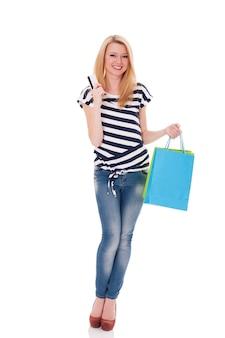 Uśmiechnięty kupujący trzyma kartę kredytową i torby na zakupy