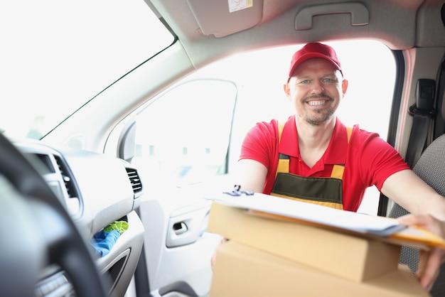Uśmiechnięty kurier wyciąga kartonowe pudełko z samochodu