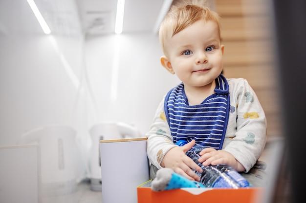 Uśmiechnięty ładny mały chłopiec z dużymi pięknymi niebieskimi oczami siedzi w pudełku na blacie kuchennym, trzymając butelkę wody i patrząc na kamery.