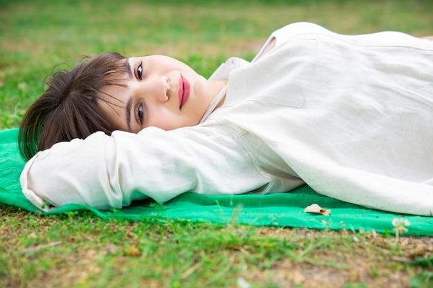 Uśmiechnięty ładny młodej kobiety lying on the beach i relaksować na gazonie