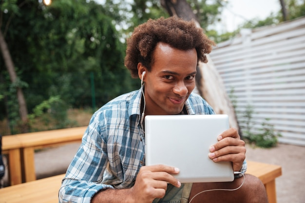Uśmiechnięty ładny młody człowiek z tabletem, słuchanie muzyki w parku