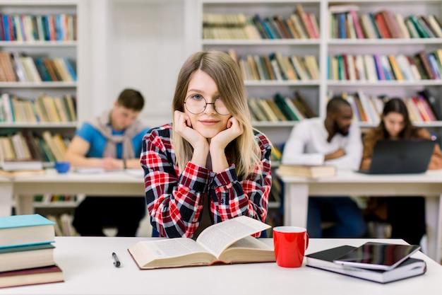 Uśmiechnięty ładny młody żeńskiego ucznia obsiadanie przy stołem w nowożytnym lekkim bibliotecznym pokoju i patrzeć kamerę
