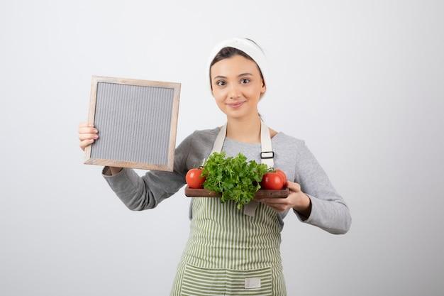 Uśmiechnięty ładny model kobieta trzyma drewnianą deskę ze świeżymi warzywami.