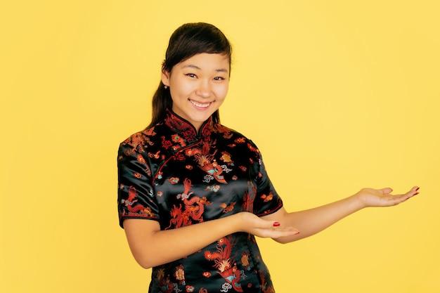 Uśmiechnięty ładny, pokazujący z boku. szczęśliwego nowego chińskiego roku. portret młodej dziewczyny azji na żółtym tle. modelka w tradycyjne stroje wygląda na szczęśliwą. świętowanie, ludzkie emocje. copyspace.