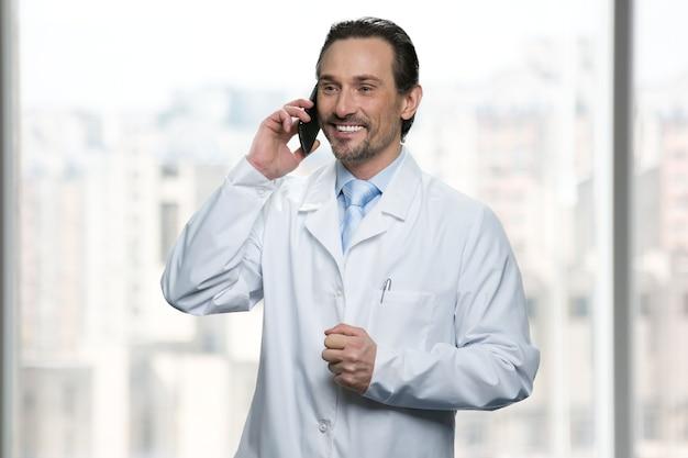 Uśmiechnięty lekarz rozmawia przez telefon. jasne okna w tle.