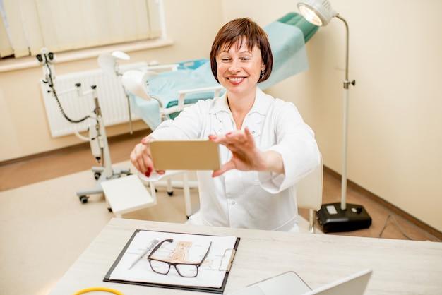 Uśmiechnięty lekarz seinor robi zdjęcie selfie siedząc w gabinecie ginekologicznym