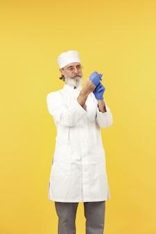 Uśmiechnięty lekarz w okularach. odosobniony. mężczyzna w niebieskich rękawiczkach.