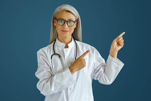 Uśmiechnięty lekarz w średnim wieku w białym mundurze wskazuje na bok, pozuje na niebieskim tle