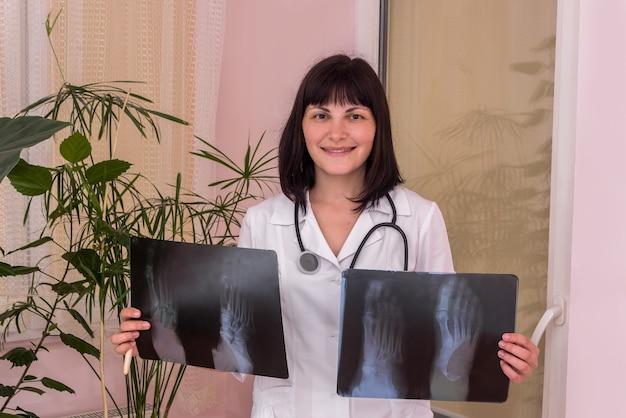 Uśmiechnięty lekarz z prześwietleniem pacjenta w rękach