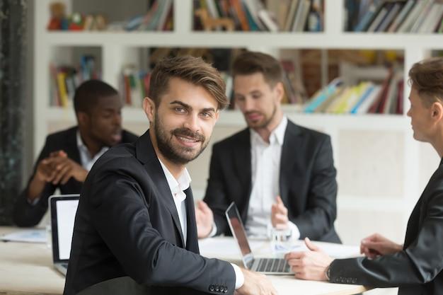 Uśmiechnięty lider zespołu patrzeje kamerę na grupowym korporacyjnym spotkaniu