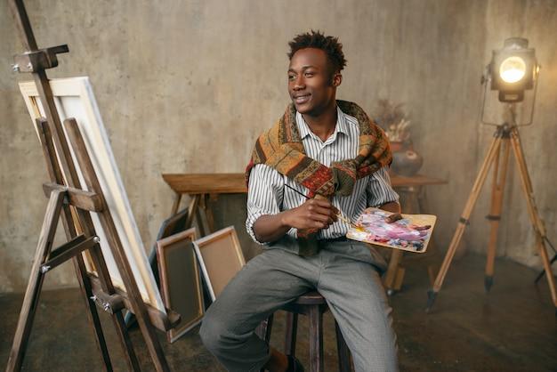 Uśmiechnięty malarz z pędzlem i paletą siedzący przy sztalugach. artysta rysuje w swoim miejscu pracy